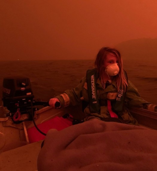 A chid being rescued on a boat amidst the Australian bushfires 2020